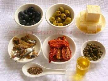 Fileti slanih sardela, kapari, masline, sušena rajčica